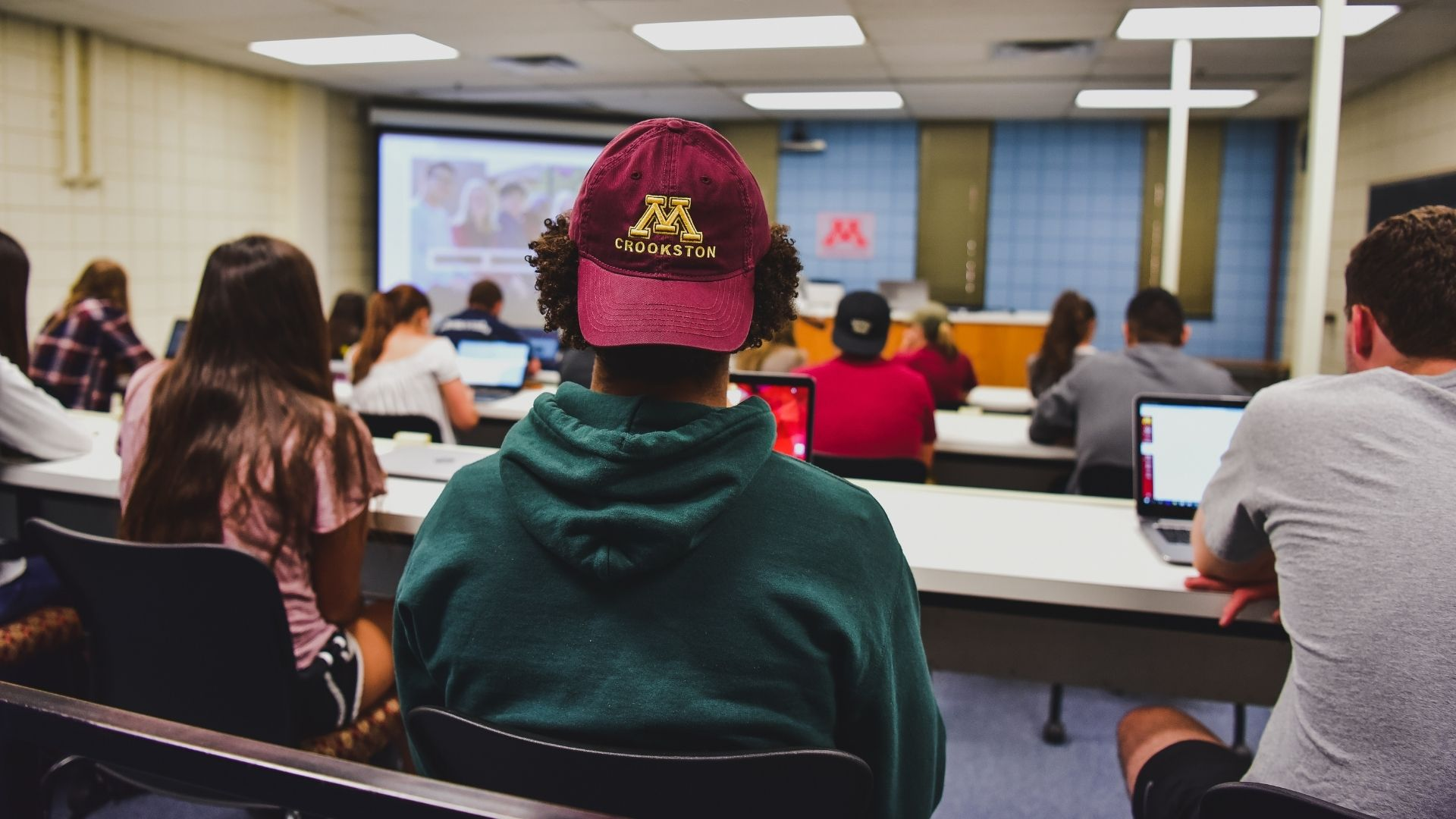 student in class with Crookston Hat on