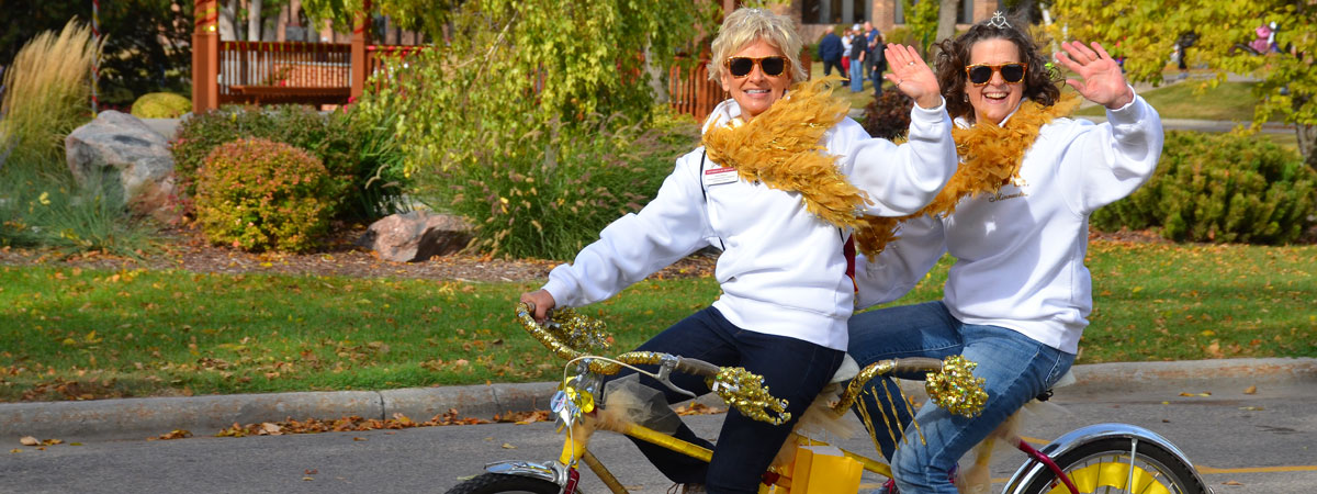 Sue and Elizabeth riding a two person bike Homecoming Parade 2015