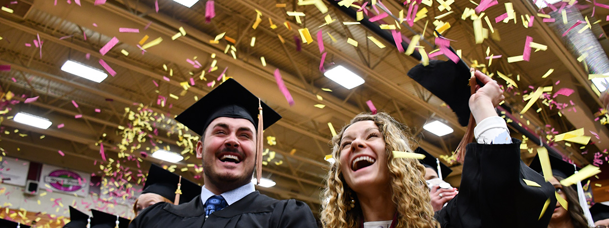 Confetti thrown at commencement with a male and female student smiling and laughing.