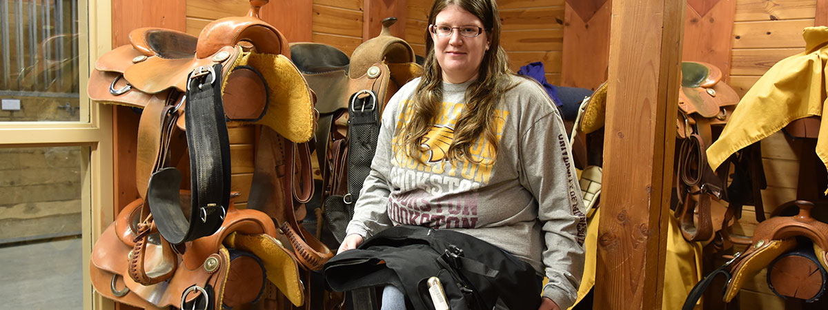 Student with specialized vest for riding horses.