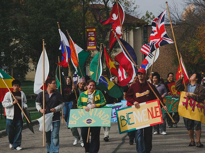 Students from different countries with their country's flags and signs walking down the Mall.