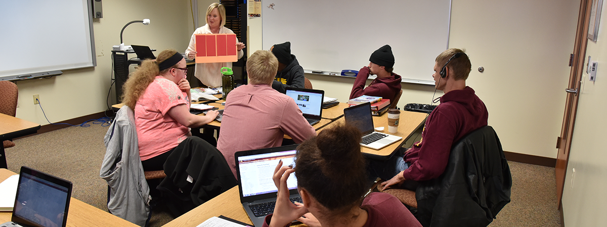 UMC Student, with documented disabilities, sitting in classroom with assistive technologies.