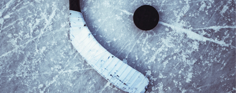 Hockey stick and puck on scratched up ice