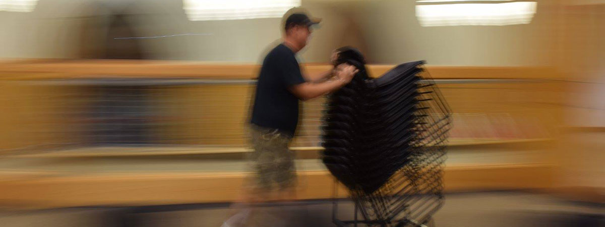 blurred image of staff moving chairs