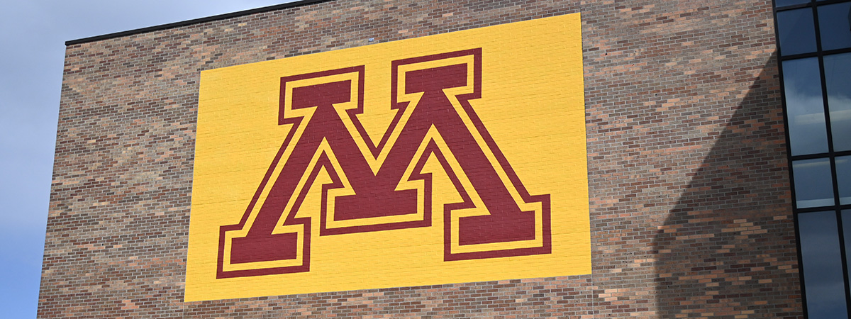 Maroon and Gold M logo on the outside of the Library Building.