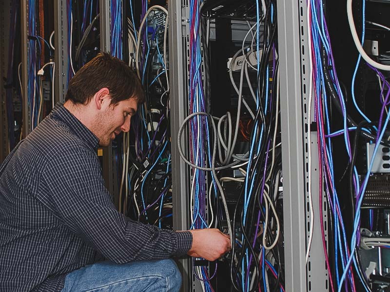 Staff person working in the Server Room on the network cables