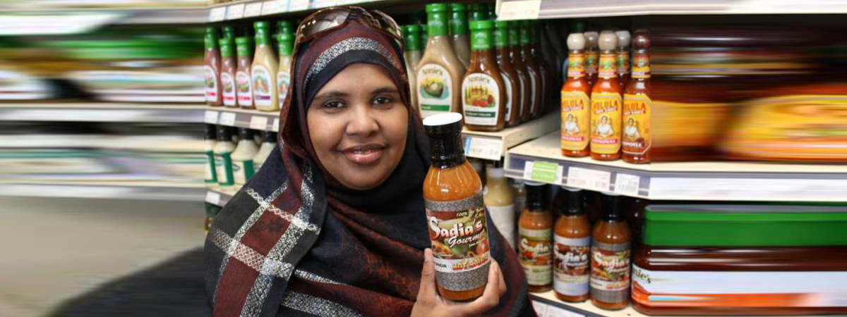 Somali business woman in a grocery store holding her product.