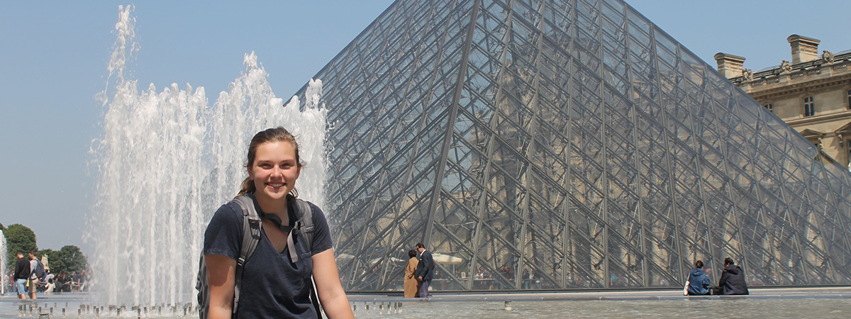 Student sitting in front of the Louvre Museum in Paris France.