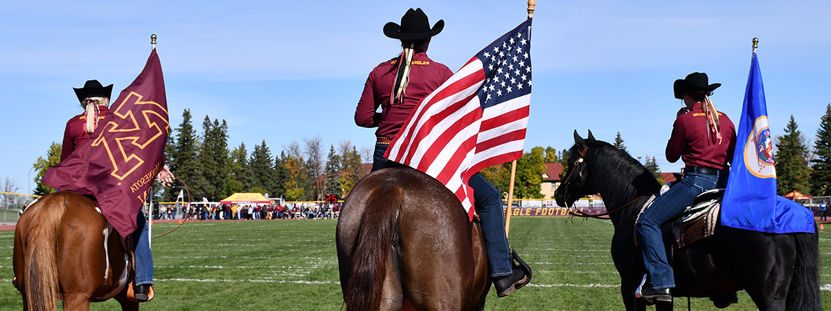 Equestrian team members with flags at the beginning of the Homecoming Game 2019