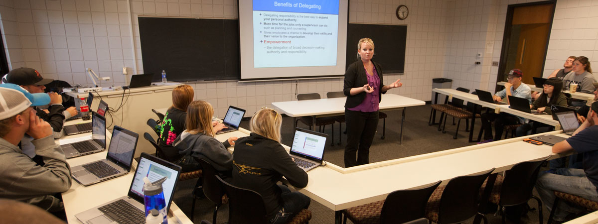 UMC Instructor teaching in front of a class in Dowell Hall.