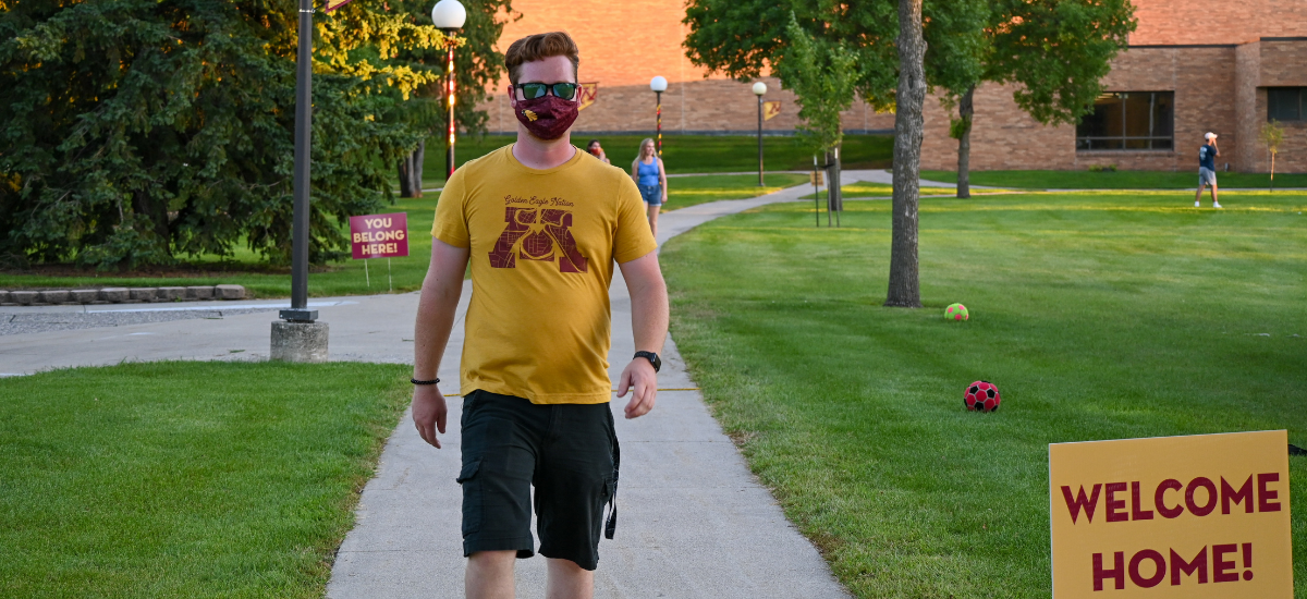 Student with mask walking through campus