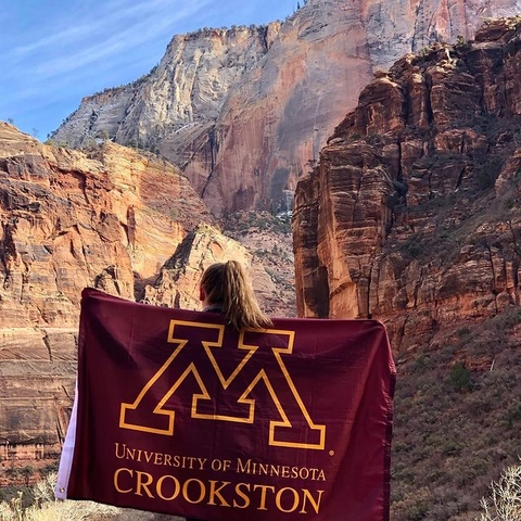 Student standing in a canyon with a UMC flag