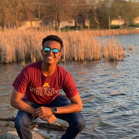 Student standing on the shore of a lake
