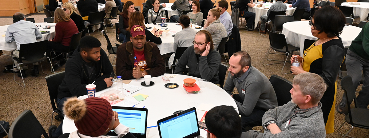 Faculty and students working at round tables during a Diversity Thursday Commons