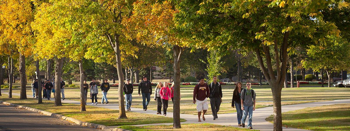 Groups of students walking outside on campus in the fall.