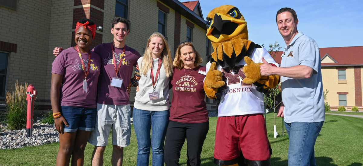 Chancellor, Vice Chancellor and students pose with Regal the Eagle
